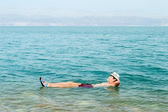 Floating in water of dead sea — Stock Photo