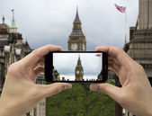 Tourist holds up camera mobile at big ben in flag — Стоковое фото