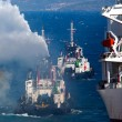 Stock Photo: Burning ship and Fire Fighting Boat sprays jets of water