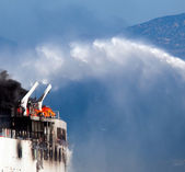 Burning ship and Fire Fighting Boat sprays jets of water — Stock Photo