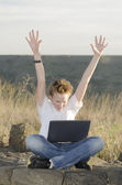 Teenager joyously throws his hands up — Stock Photo