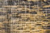 Falling water stream against stonework rough texture — Stock Photo