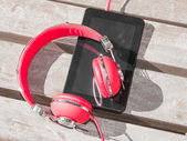 Red colored headphones and tablet PC — Stock Photo