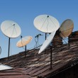 Roof full of satellite dishes — Stock Photo