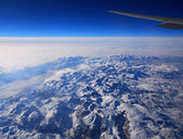 Wing of an airliner over the mountains — Stock Photo