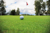 Golf ball in front of flag — Stock Photo