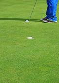 Hit a golf ball legs — Stock Photo