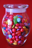Glass Jar Full of Candy Against a Red Background — Stock Photo
