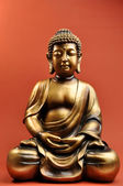 Bronze Buddha Statue Against a Red Orange Background — Foto Stock