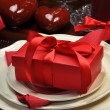 Romantic Valentine Dinner Table Setting with Gift Closeup - Stock Photo