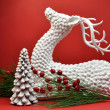 White Reindeer and Christmas Tree Against Red Background - Stock Photo