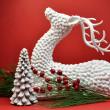 Renne blanc et le sapin de Noël sur fond rouge — Photo