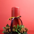 Red candle with holly and pine cone Christmas table centerpiece — Stock Photo #18292529