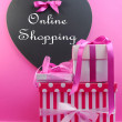 Stack of pink gift boxes with heart blackboard Online Shipping sign. — Stock Photo