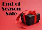 """End of Season Sale"" with black box gift on red background. — Stock Photo"