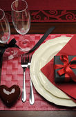 Formal Valentine dinner table setting for one with champagne glasses gift — Stock Photo
