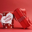 """Valentines Day """"With love"""" message on red polka dot mug and red gift with red bow — Stock Photo"""
