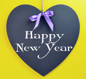 Happy New Year message on heart blackboard against a yellow background. — Stock Photo