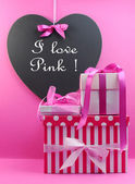 """""""I love pink"""" message written a heart blackboard with stack of pink gifts — Stock Photo"""