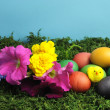 Colorful rainbow eggs with yellow chick and pretty flowers on green grass moss - Stock Photo