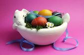 Ovos de páscoa de cor de arco-íris em tigela de coelho coelhinho branco com fita de bolinhas azul em um fundo rosa. — Foto Stock