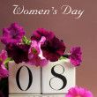 White block calendar for International Women&#039;s Day, March 8, decorated with pink and purple flowers (vertical) - Stock Photo
