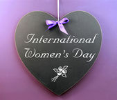 International Women's Day message written on heart shape blackboard sign — Stock Photo