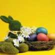 Yellow theme Happy Easter still life with grass bunny rabbit with rainbow color eggs in a nest — Stock Photo