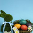 Blue theme Happy Easter still life with grass bunny rabbit with rainbow color eggs in a nest — Stock Photo