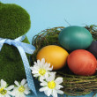Stock Photo: Blue theme Happy Easter still life with grass bunny rabbit with rainbow color eggs in a nest