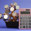 Money Tree concept with coins hanging from a crystal tree with pink calculator against a blue background. — Stock Photo