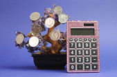 Concepto de árbol de dinero con monedas colgando de un árbol de cristal con rosa calculadora contra un fondo azul. — Foto de Stock
