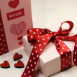 Handmade gift card with pink gift and red polka dot ribbon and heart on white natural wood table. — Stock Photo