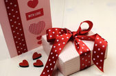 El yapımı hediye kartı ile pembe hediye ve kırmızı puantiyeli şerit ve kalp üzerinde beyaz doğal ahşap masa. — Stok fotoğraf