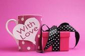 Cute and sassy pink mug and gift with polka dot ribbon and 'with love' message on heart shape gift tag. — Stock Photo