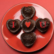 Romantic love theme mini choolate cupcake muffins with letter spelling I Love (heart) You, on red red plate and background. — Stock Photo