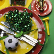Soccer football celebration party table settings in red, green and yellow team colors. Vertical portrait orientation. — Stock Photo