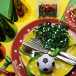 Soccer football celebration party table settings in red, green and yellow team colors. — Stock Photo