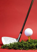 Golfing concept with iron, ball and tee on red background, vertical with copy space. — Stock Photo