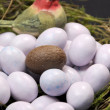 One chocolate Easter egg in bird's nest with sugar coated candy marble eggs. Vertical close-up. — Stock Photo