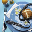Happy Easter dinner table setting with blue polka dot plates, and decorations against a blue background. Vertical with Easter Hot Cross Bun and color boiled eggs. — Stock Photo