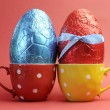 Two large bright color red and blue foil wrapped chocolate Easter Eggs in red and yellow polka dot tea cups against a red background. - Stock Photo