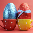 Two large bright color red and blue foil wrapped chocolate Easter Eggs in red and yellow polka dot tea cups against a red background. — Stock Photo #20247453