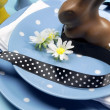 Happy Easter dinner table setting with blue polka dot plates, and decorations against a blue background. Vertical close-up with chocolate Easter bunny rabbit. — Stock Photo #20247457