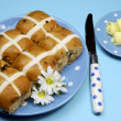 Traditional Australian and English Good Friday meal, Hot Cross Buns, on blue polka dot plate with knife and butter curls on blue background. — Stock Photo #20247549