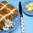 Traditional Australian and English Good Friday meal, Hot Cross Buns, on blue polka dot plate with knife and butter curls on blue background. Vertical aerial orientation. — Stock Photo #20247553