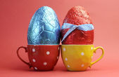 Two large bright color red and blue foil wrapped chocolate Easter Eggs in red and yellow polka dot tea cups against a red background. — Stock Photo