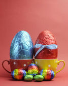 Two bright color red and blue foil wrapped chocolate Easter Eggs in red and yellow polka dot tea cups. Vertical with copy space for your text here. — Stock Photo