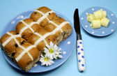 Traditional Australian and English Good Friday meal, Hot Cross Buns, on blue polka dot plate with knife and butter curls on blue background. — Stock Photo