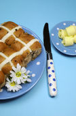 Traditional Australian and English Good Friday meal, Hot Cross Buns, on blue polka dot plate with knife and butter curls on blue background. Vertical aerial orientation. — Stock Photo